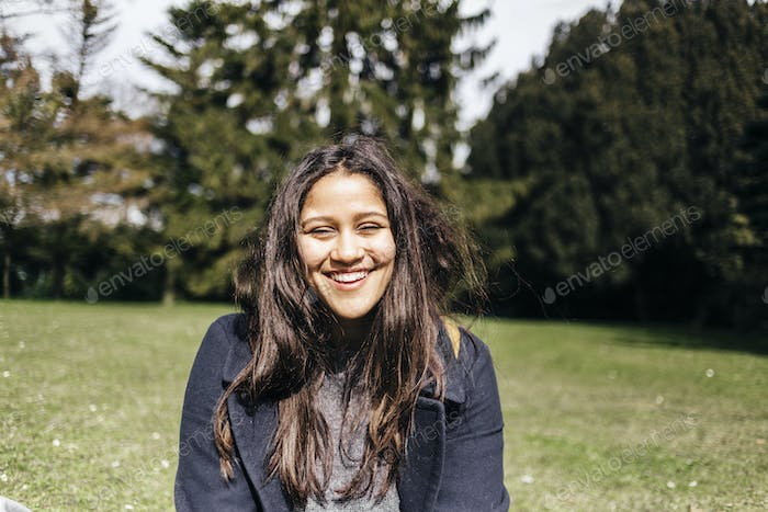 Portrait of happy young woman sitting in park