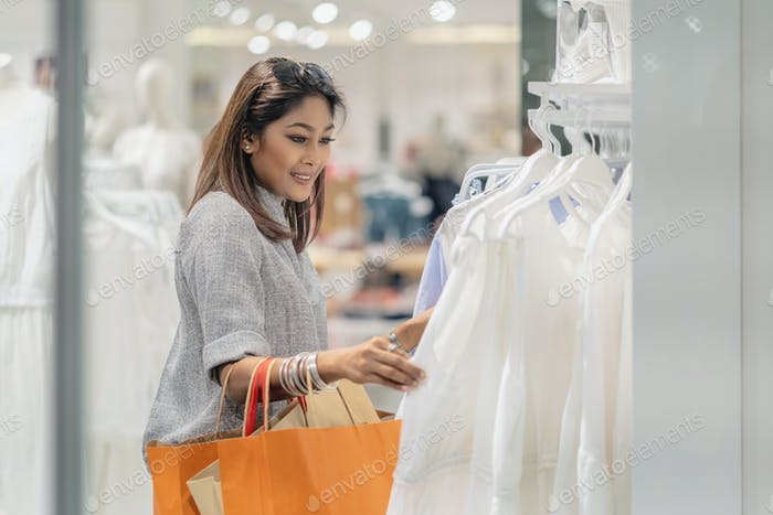 Happy Asian woman choosing clothes with reflection of glass in store shop with happy