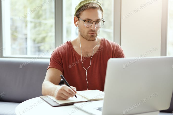 Concentrated bearded young European hipster in stylish round glasses and green hat looking at laptop