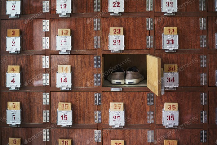 A row of shoe lockers with one open door, and one pair of shoes stored.