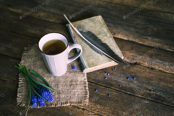 Cup of tea with blue flowers and a book on wooden background. Vintage