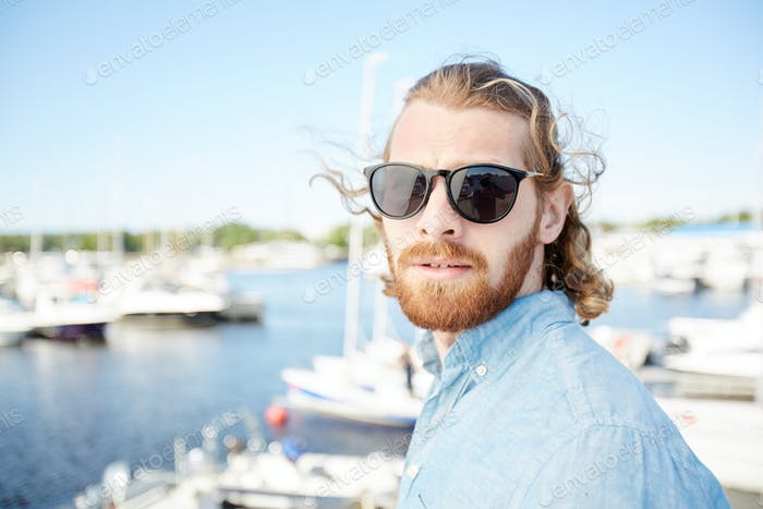 Handsome man in sunglasses visiting yacht club
