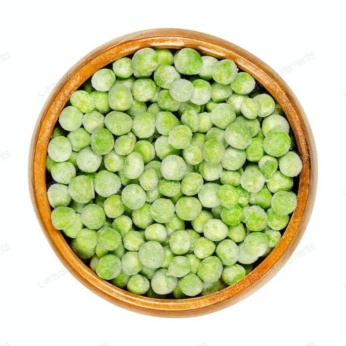 Frozen green peas, seeds of Pisum sativum in wooden bowl