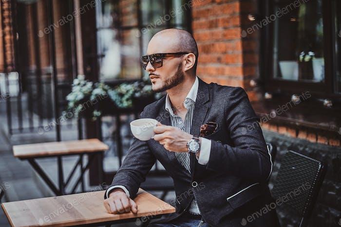 Attractive groomed man is enjoying coffee
