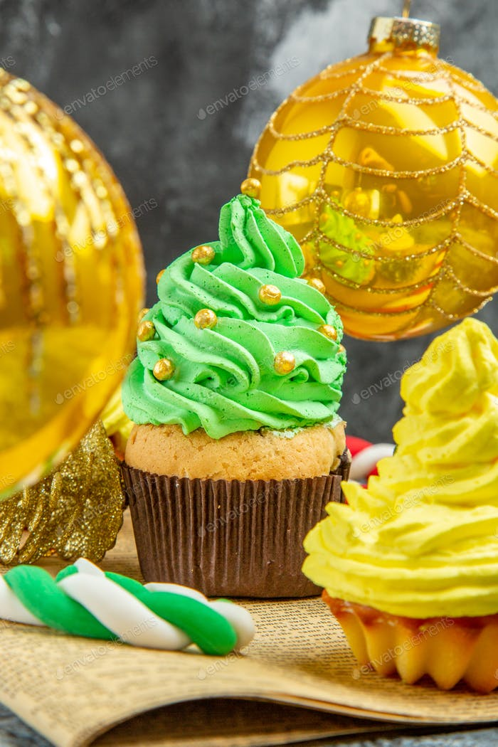 front view mini colorful cupcakes xmas tree toys xmas candies on newspaper on dark background new