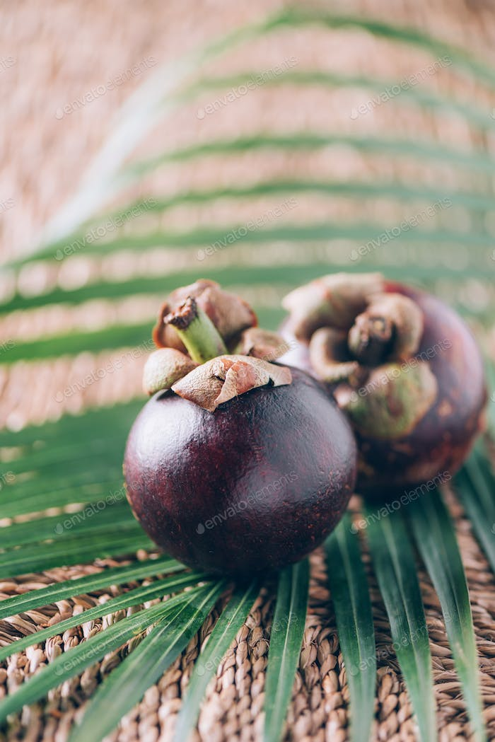 Mangosteen with palm leaves on rattan background. Copy space. Tropical travel, exotic fruit. Vegan