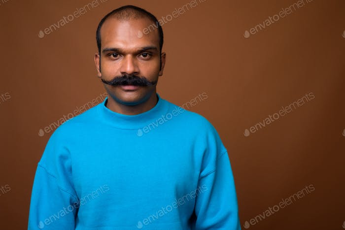 Face of Indian man with mustache wearing blue sweater