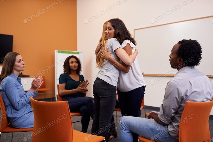 Two Women Hugging As Group Of Men And Women At Mental Health Group Therapy Meeting