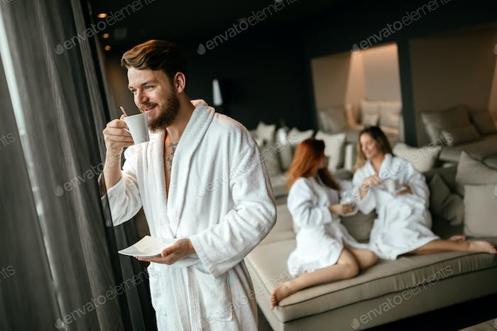 Handsome male in bathrobe drinking tea