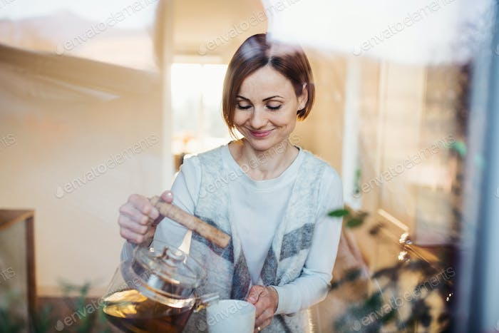 A young woman standing indoors in kitchen, pouring tea. Shot through glass.