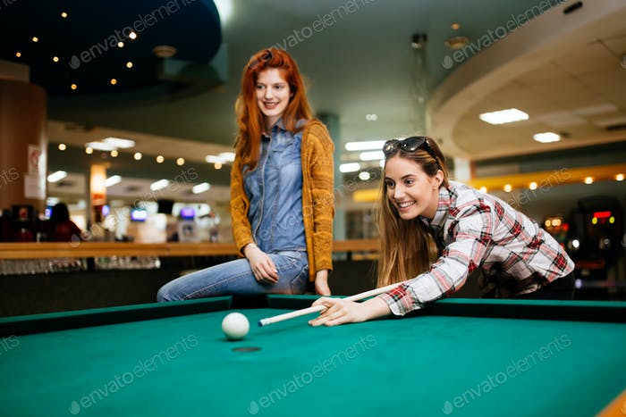 Beautiful women playing billiards
