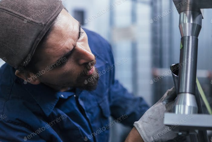 Close-up of bearded worker constructing bike
