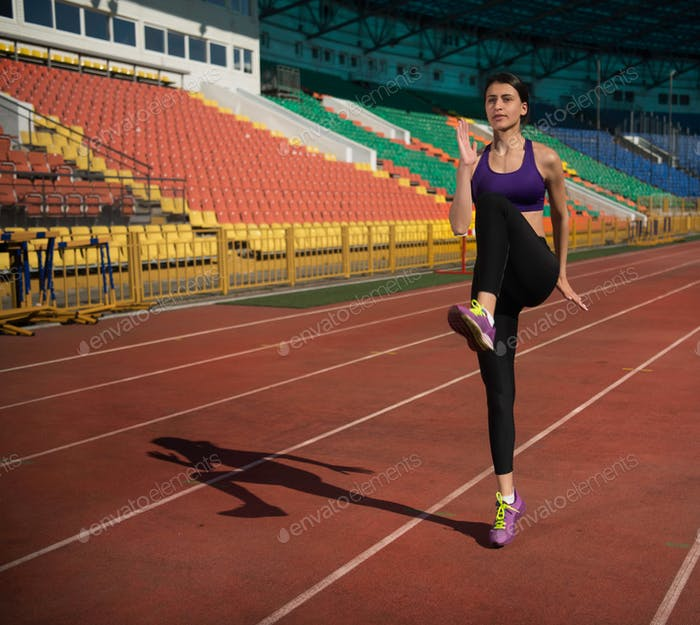 track and field woman doing exercise at the stadium