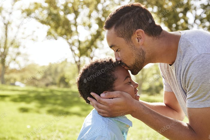 Close Up Of Father Kissing Son In Park