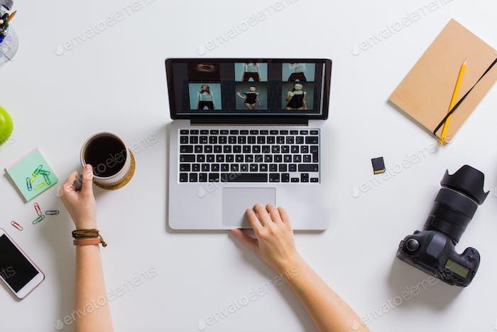Frau Hände mit Kamera arbeiten auf Laptop am Tisch