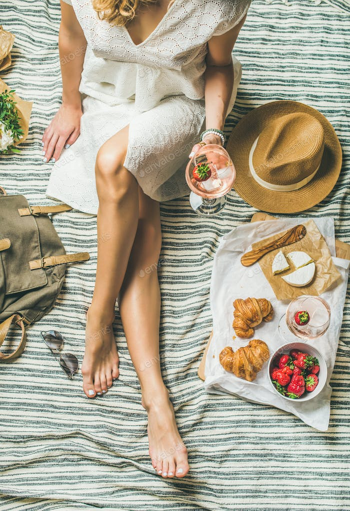 Woman in dress sitting on blanket with wine and snacks