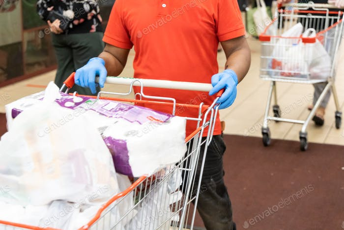 New normal lifestyle with shoppers put on disposable gloves in supermarket