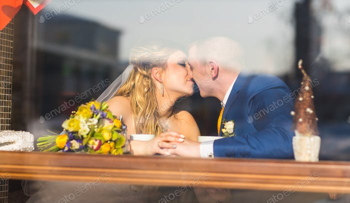 Cute married couple in cafe, groom kissing a bride. Pure tenderness.