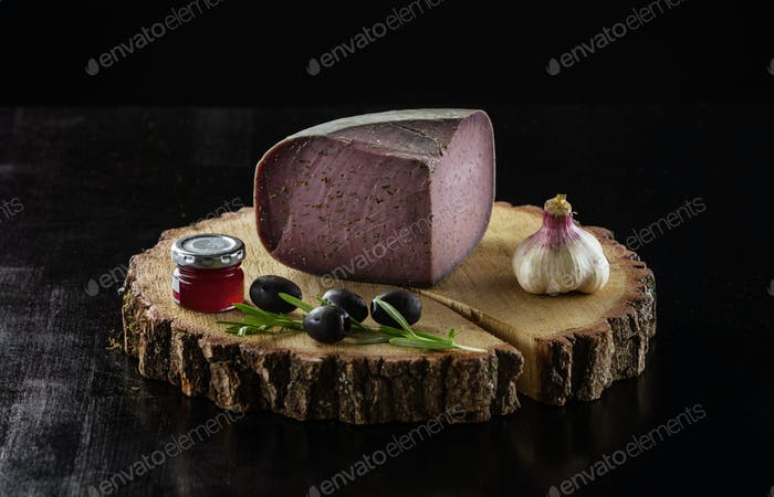 Piece of cheese with lavender, jar of jam, olives and garlic on