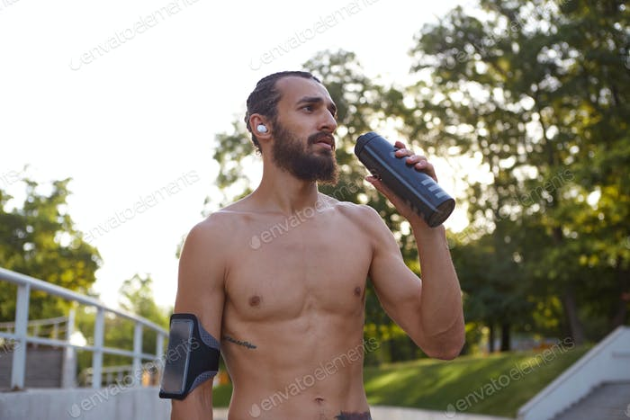Young attractive bearded guy has extreme sport in park, drinking water