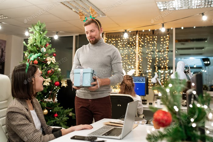 Young businessman with xmas headband giving present to one of colleagues