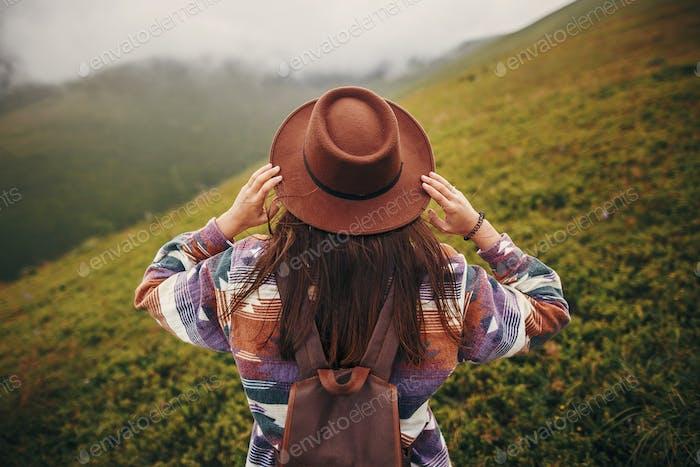 Happy stylish Reisender Mädchen hält Hut mit Rucksack und windigen Haaren in Bergen Wolken