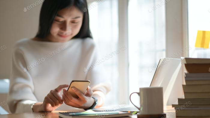Image of young professional professional looking for information on smartphone in beautiful office.