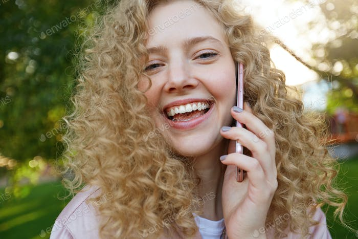 Close up photo of beautiful girl blonde, speaking with someone on phone