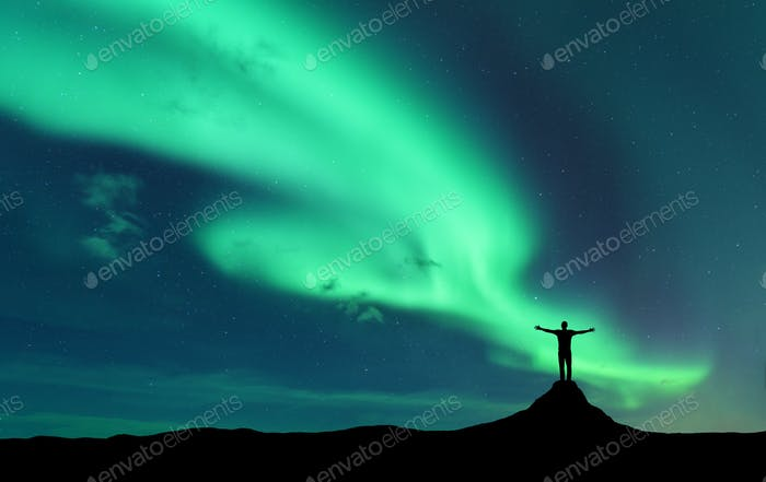 Aurora and silhouette of standing man with raised up arms on the mountain in Norway