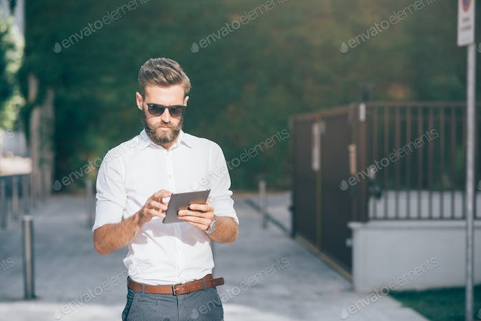 Knee figure of young handsome bearded businessman holding a tablet