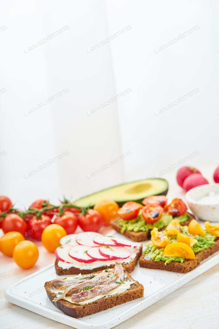 Set of smorrebrods with fish, anchovies, avocado, tomatoes, radish. Side view, copy space,