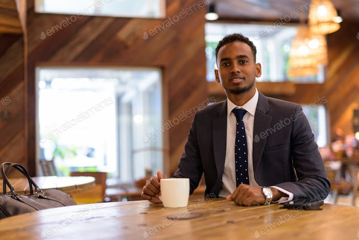 Young African businessman relaxing inside coffee shop