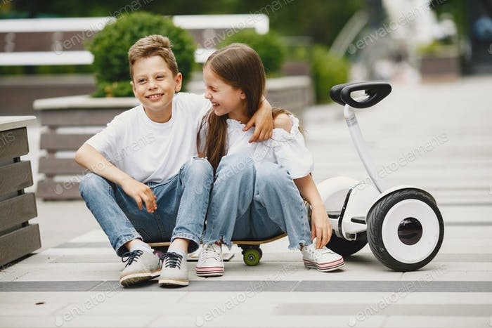 Children learn to ride hoverboard in a park on sunny summer day
