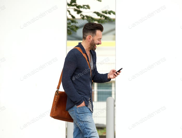 Happy mature man on the city street using cell phone