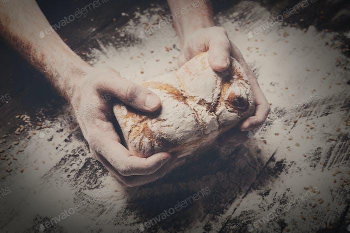 Bäckerei Konzept Hintergrund. Hände halten Brotlaib