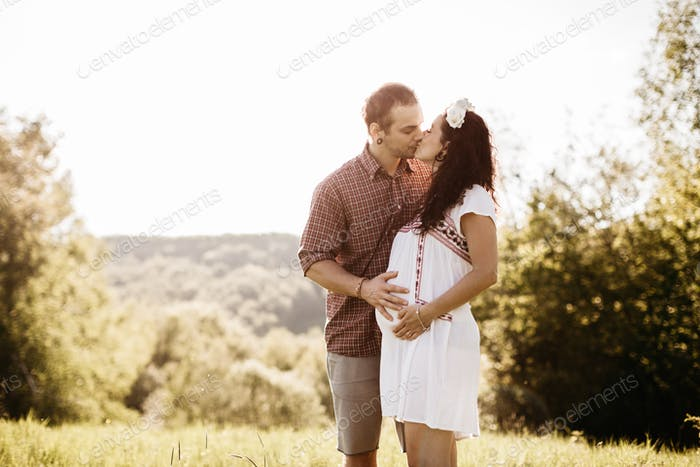 Happy pregnant couple hugging and kissing