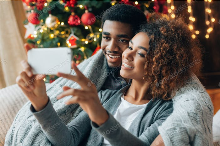 Young loving couple making selfie with Christmas tree