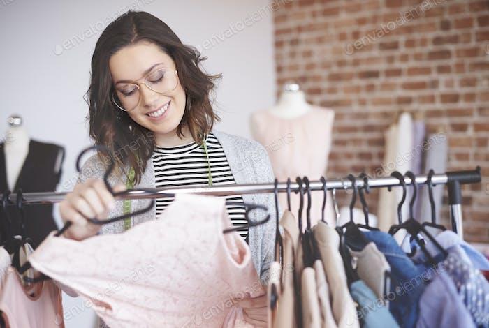 Modedesigner sucht Outfits auf Kleiderständer