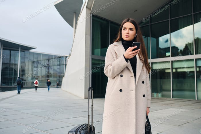 Young businesswoman in coat thoughtfully using cellphone waiting on city street with suitcase