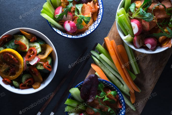 Marinated vegetables in bowls and chopsticks close-up. Asian cuisine