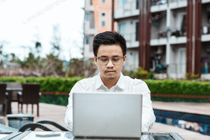 Business Concept - Young Business man plan project on his property with laptop
