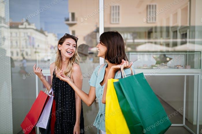 Glückliche Freundinnen, die Spaß haben und in der Stadt einkaufen
