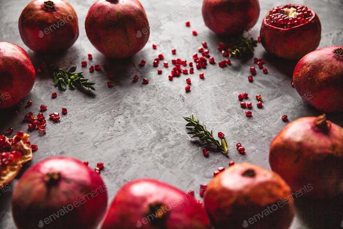 Granatapfelfrucht. Reifer und saftiger Granatapfel auf rustikalem grauen Hintergrund