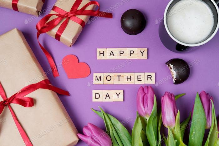 Blumenstrauß aus lila Tulpen, Geschenkbox und Holzbuchstaben auf violettem Hintergrund.