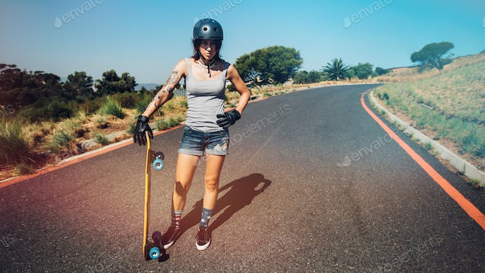 Young woman with a longboard on countryside highway