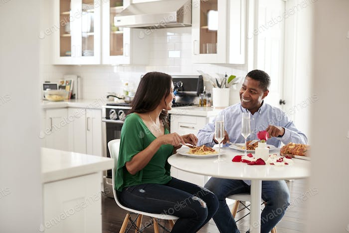 Middle aged mixed race couple eating a romantic meal together in their kitchen, close up