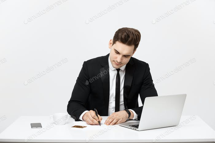 Business Concept: Portrait concentrated young successful businessman writing documents at bright
