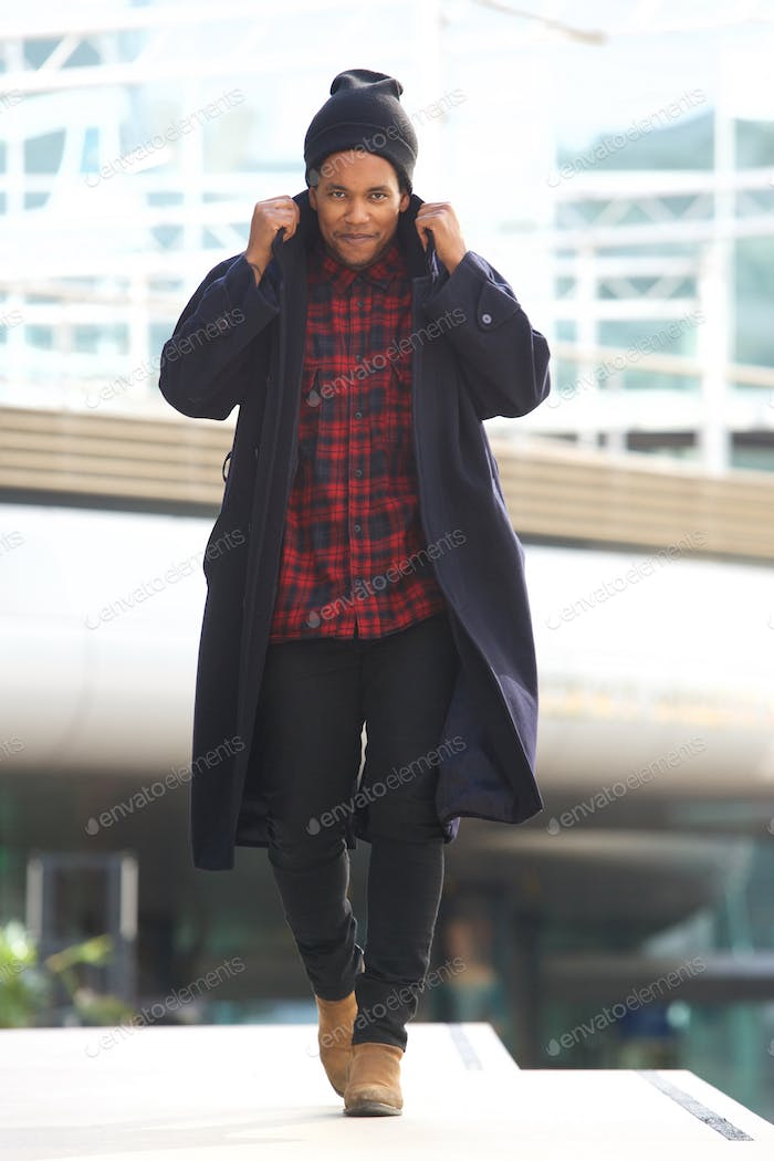 Full body cool african american walking with winter jacket and beanie in the city