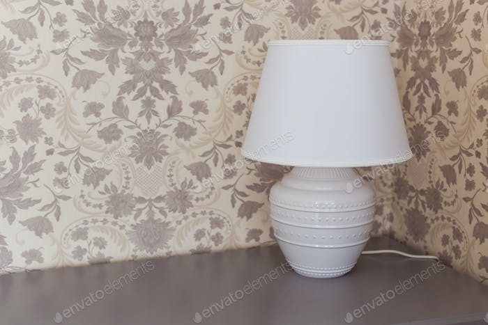 White lamp on the nightstand close-up. Interior concept.