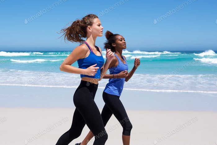 Two young women running along the beach